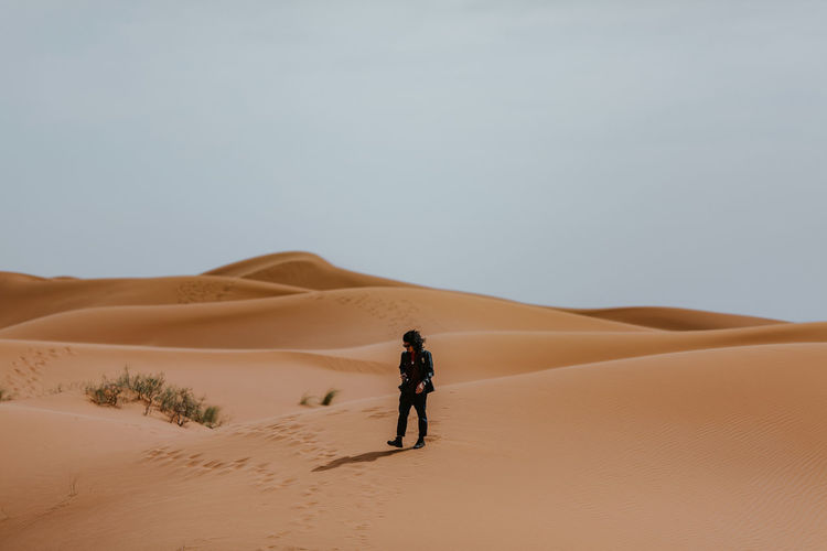Man walking on sand in desert against sky