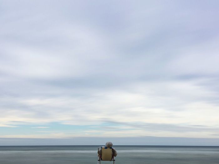 Rear View Of Person Sitting On Beach Against Sky