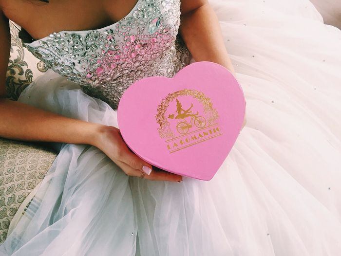 Midsection of bride holding heart shape gift
