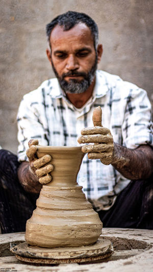 Man making pottery while sitting outdoors