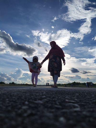 Full length of women standing on landscape against sky