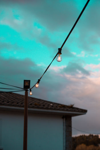 Low angle view of illuminated light bulbs hanging against building