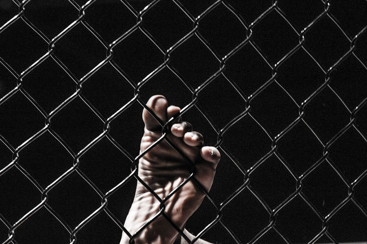 Close-up of barefoot on chainlink fence