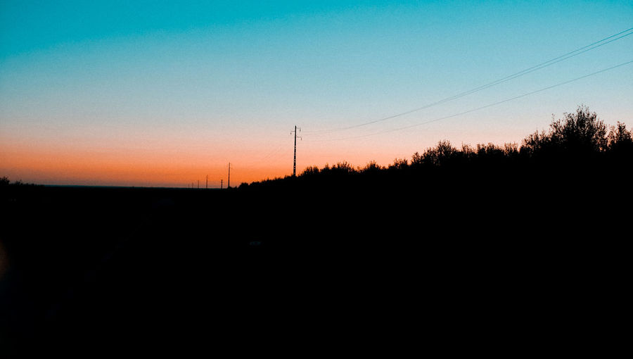 Silhouette of electricity pylon against sky during sunset