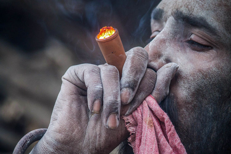Close-up of man holding cigarette against blurred background