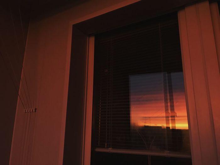 Building seen through window during sunset