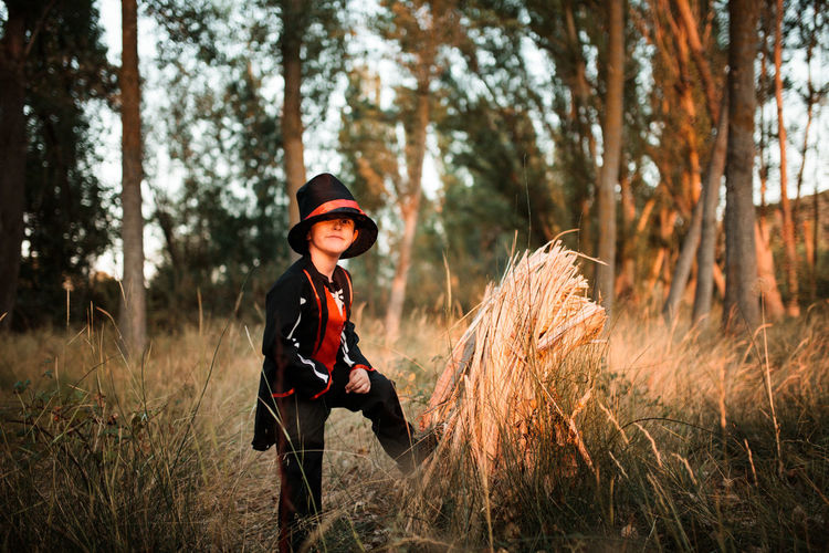 Full length of man wearing hat on field in forest