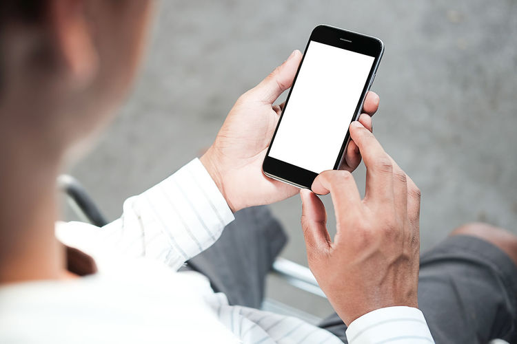 Midsection of man holding blank mobile phone