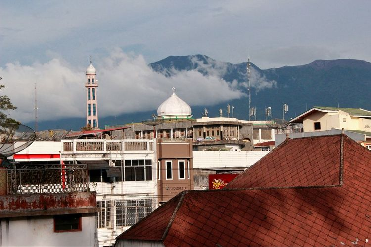 Houses and mosque against cloudy sky