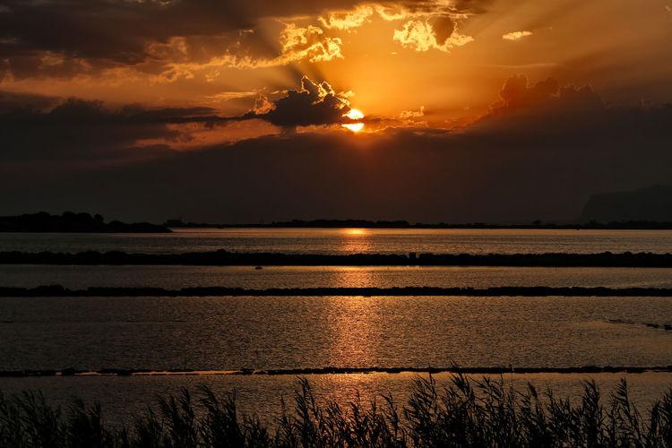 Idyllic shot of salt flats against orange sky during sunset