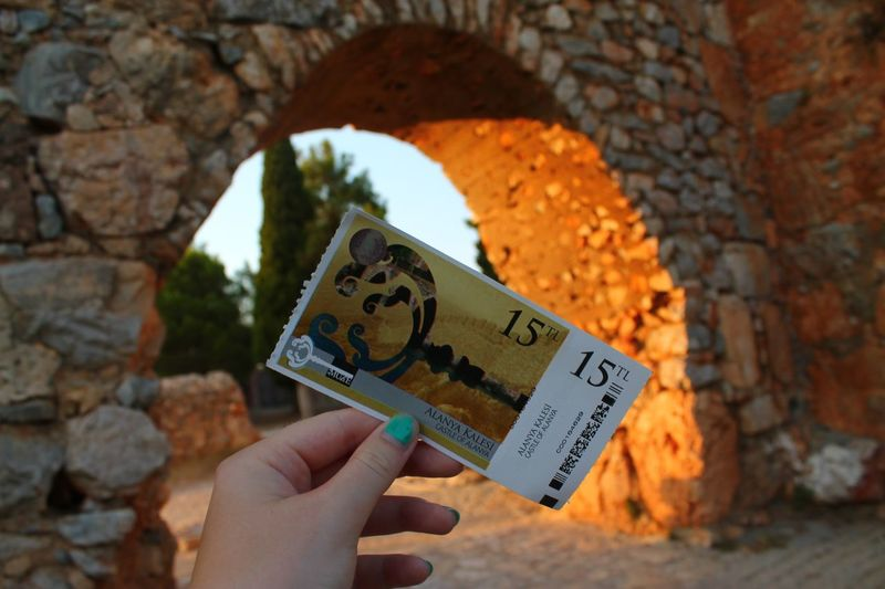 Ticket to Alanya Kalesi Ancient Architecture Arch Castle Ticket Human Hand Holding Hand One Person Human Body Part Photography Themes Focus On Foreground Leisure Activity Human Finger Finger Real People Communication Unrecognizable Person Close-up Body Part Personal Perspective Day Lifestyles Nature My Best Travel Photo