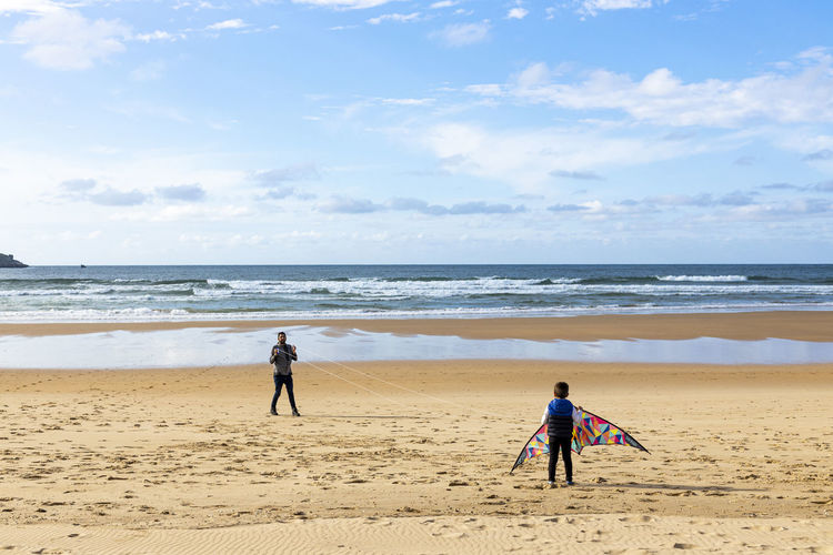 People playing with kite at beach against sky