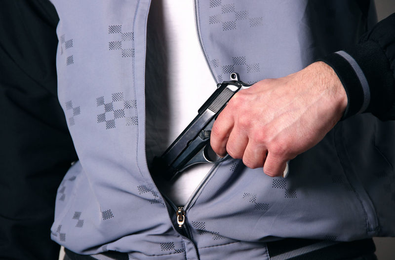 Midsection of man with gun