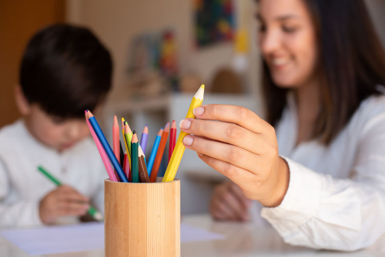 Midsection of woman holding multi colored pencils on table
