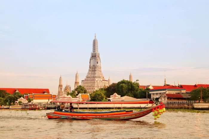 Bangkok. Wat Arun. Chao Phraya River. Wat Arun (Temple Of Dawn) Wat Arun, Bangkok Thailand Chao Phraya River Side Chao Phaya River Bangkok Thailand. River Riverside ASIA Asian Temple Religion Buddhism Buddha Tourism Tourist Place Of Worship Religion Beauty Arts Culture And Entertainment Water Arrival Sky Architecture Landscape Travel Boat Praying Pagoda