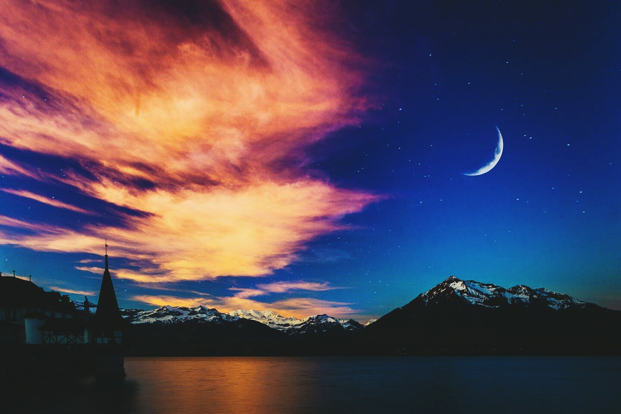 sky, water, scenics, waterfront, beauty in nature, tranquil scene, mountain, tranquility, built structure, night, architecture, nature, silhouette, dusk, idyllic, illuminated, cloud - sky, sea, river, mountain range