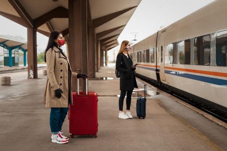 Full length of women wearing mask standing on railroad platform
