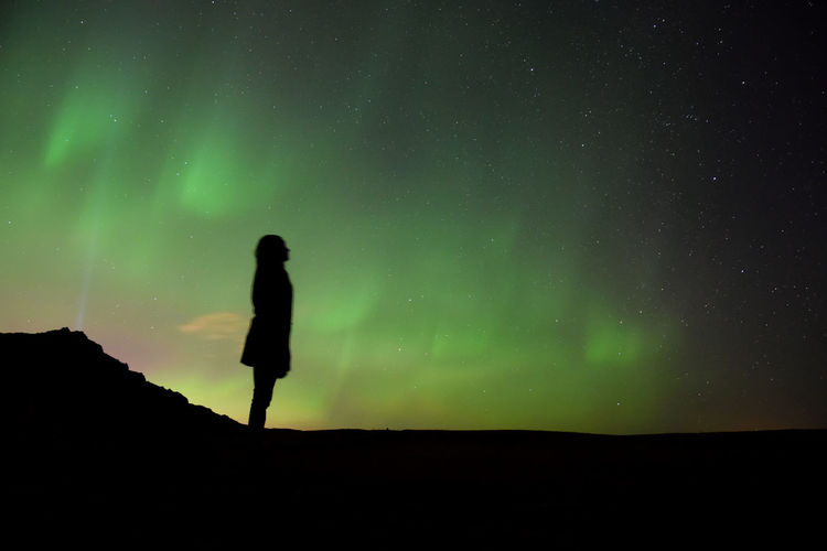 Silhouette woman against background of northern lights