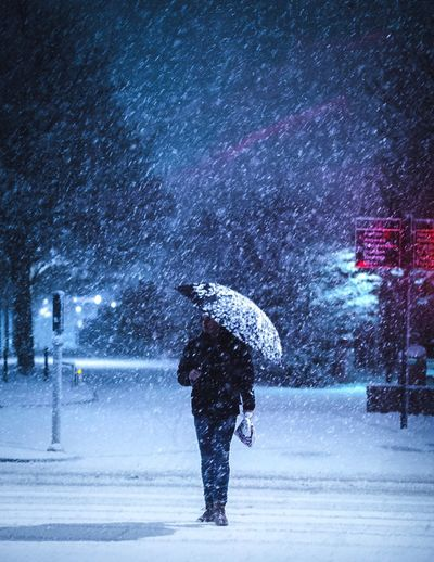 Man with umbrella on snow covered street