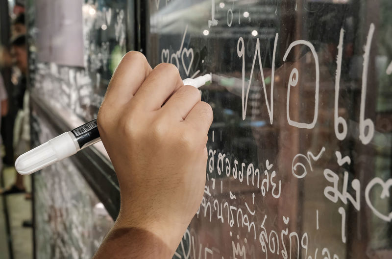 Cropped image of hand writing on glass window