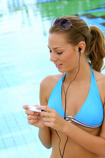 young blond woman listening to music with MP3 players at the pool Beautiful Happy Holiday Listening Music Music Summer Holidays Woman Bikini Blond Girl Happyness Leisure Leisure Activity Lifestyles Mp3 Player One Person Outdoors Pretty Relaxation Swimming Pool Vacation Water Wellbeing Young Adult Young Women