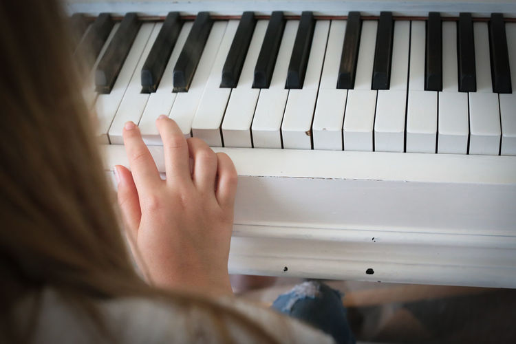 Cropped image of woman playing grand piano at home