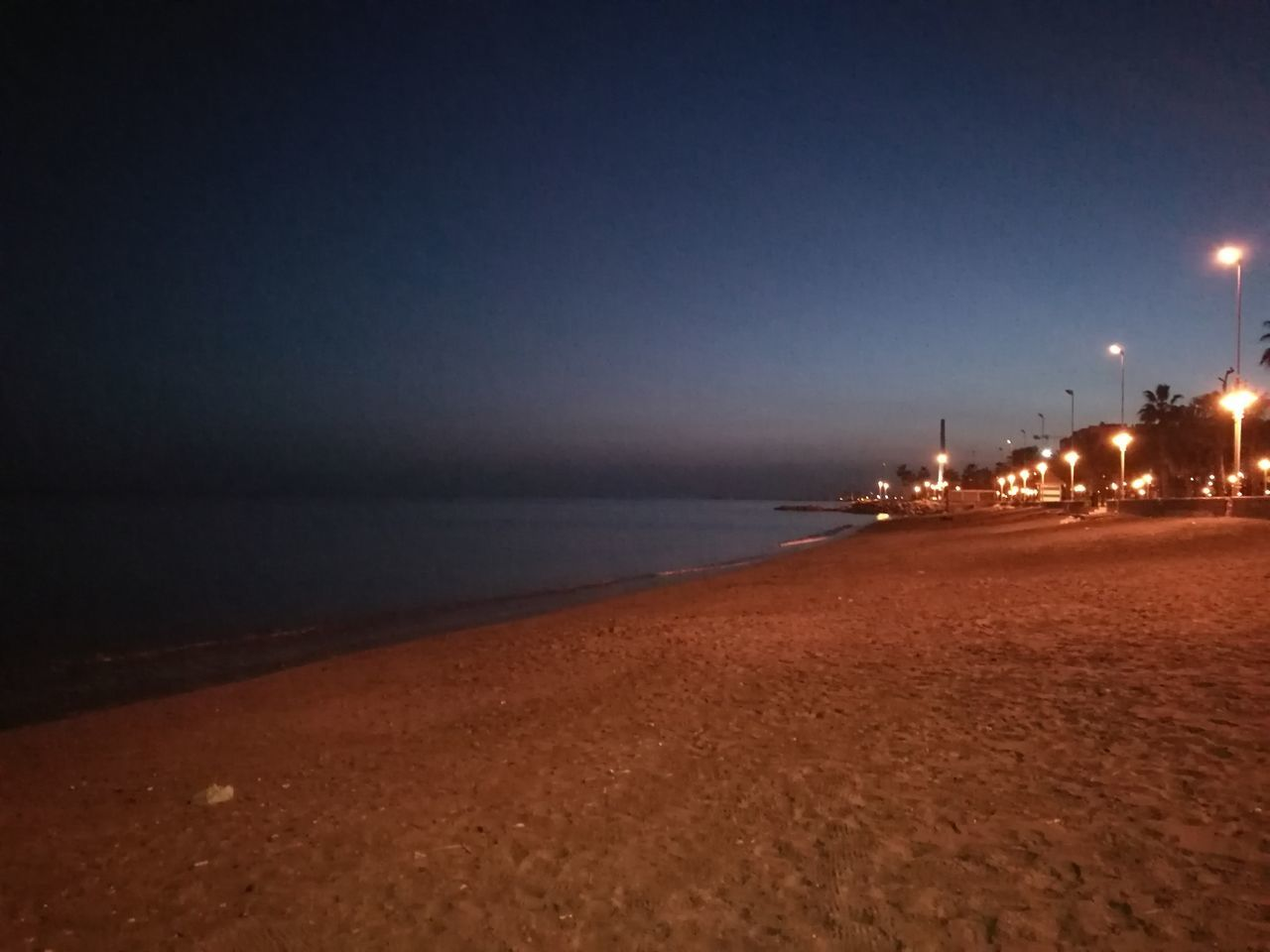 illuminated, sea, night, beach, water, dusk, no people, sky, tranquility, outdoors, horizon over water, sand, scenics, nature, beauty in nature, oil industry, clear sky, architecture, city