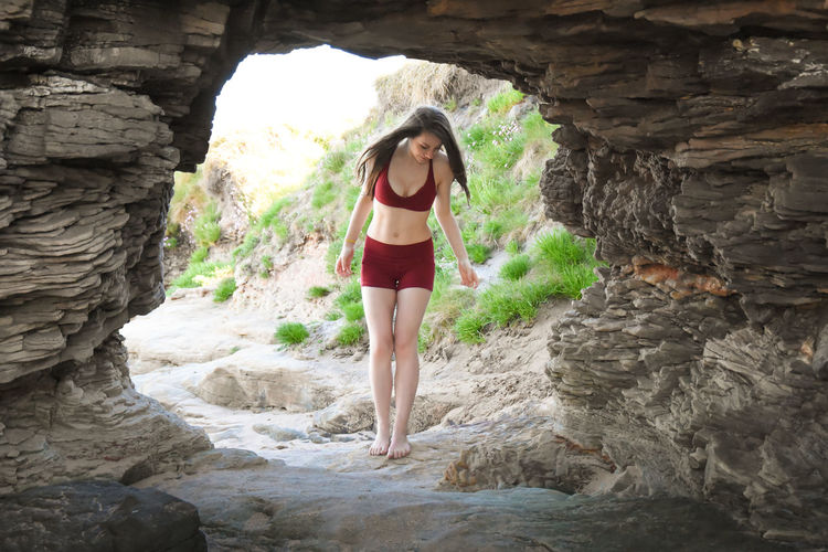 Full length of young woman standing in cave