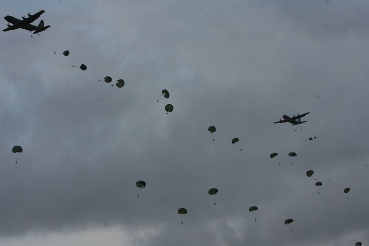 Low angle view of paratroopers parachuting from aircraft against cloudy sky