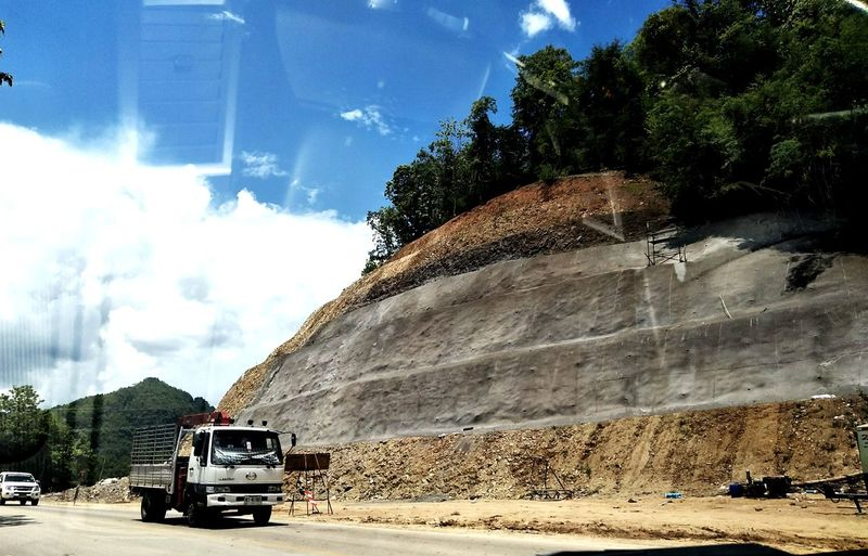 The sky road. Tree Land Vehicle Road Construction Site Construction Vehicle Sand Sunlight Construction Machinery Industrial Equipment Sky Dump Truck Quarry Road Construction Tractor Mine Combine Harvester Agricultural Machinery