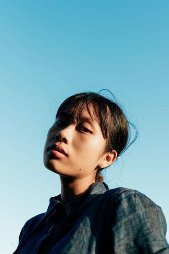 Portrait of woman looking away against blue sky
