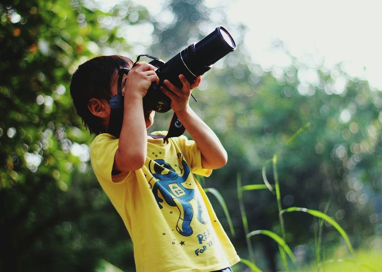 Boy photographing with digital camera