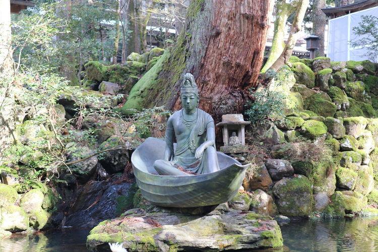 Statue amidst rocks against plants