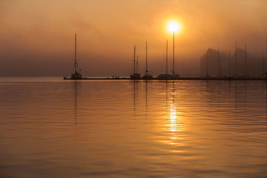 Sunrise in the city port of Rostock, Germany. Cityscape Harbor Marina Misty Morning Reflection Relaxing Rostock Sailing Ship Fog Idyllic Journey Port River Sailboat Sailing Boat Sunrise Sunup Tourism Town Travel Destinations Vacation Warnow Water
