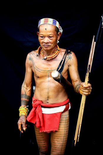 Shirtless mature man holding sticks against black background