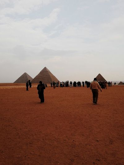 People walking at great pyramid of giza against sky