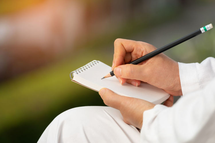Hand writing on note pad. Woman hands holding blank note writing with black pencil relaxing in garden backyard at sunrise ,natural blurred background. Dear Mom Hands Woman Writer Blank Note Diary Idea Memorandum Missing Someone Note Pad Pencil Drawing Working Outside