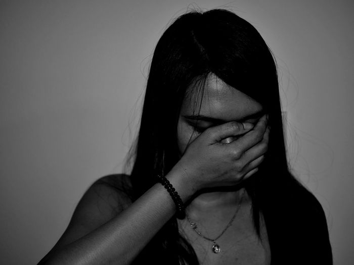 Close-Up Of Woman Covering Mouth Against Wall