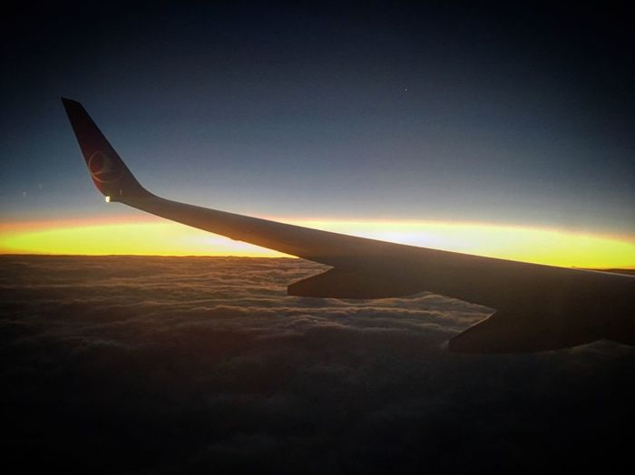 Silhouette airplane wing against sky during sunset