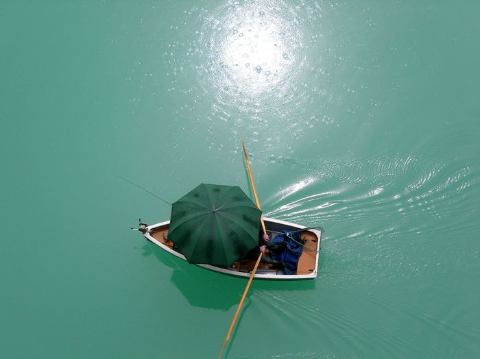 High Angle View Of Person Covered With Umbrella Sailing Boat In Lake
