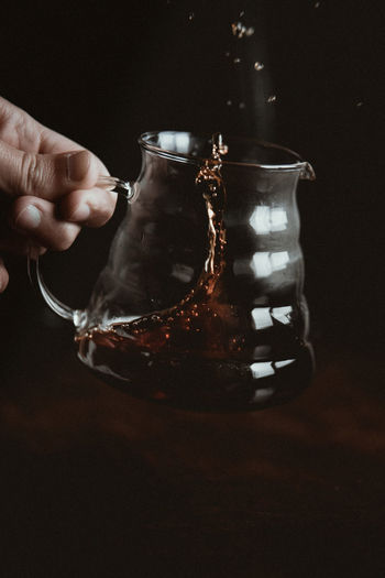 Cropped image of hand holding black tea in glass jar