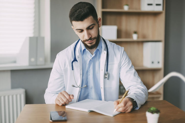 Friendly young male doctor of oriental appearance sits at a desk in his office and takes notes