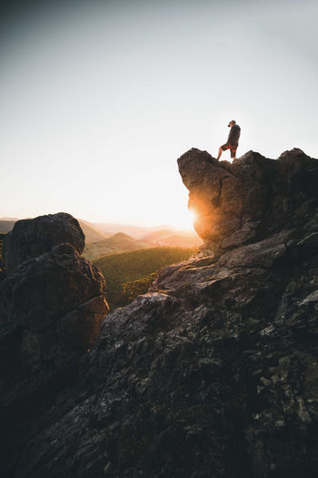 Man on rock by mountains against sky