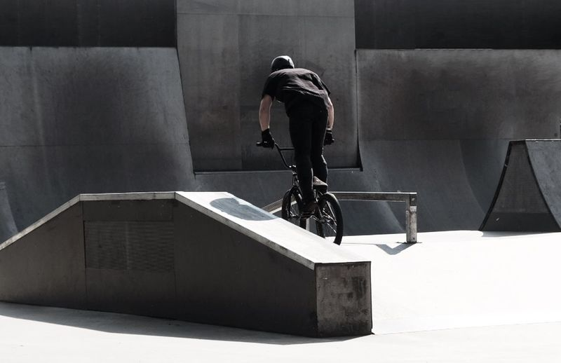 Rear View Of Man Doing Stunt On Bicycle At Skateboard Park