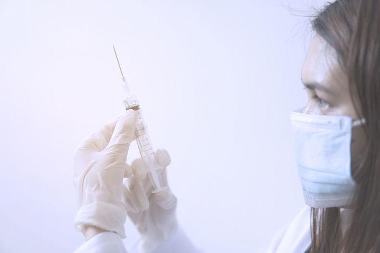 Close-up of doctor wearing mask holding syringe against white background