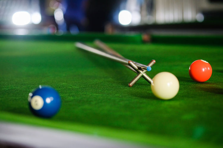 Midsection of man playing pool at club
