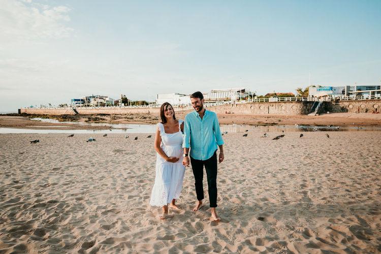 Couple kissing on beach against sky