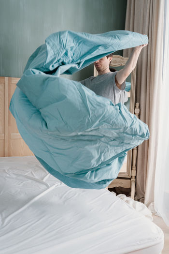 Adult man is putting the bedding cover or mattress pad on the bed. regular bed linen change