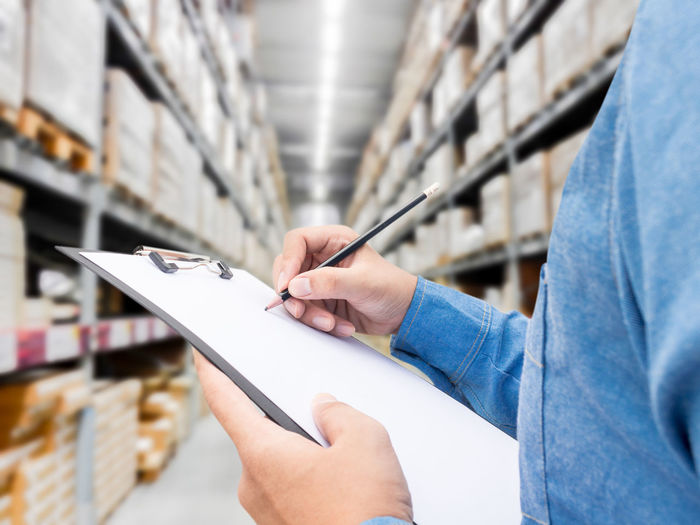 Midsection of man writing in checklist by shelves