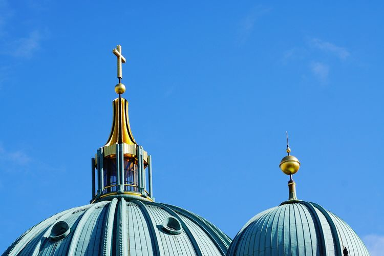 High section of berlin cathedral against blue sky on sunny day